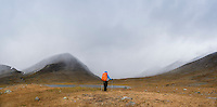 Female hiker watches as autumn snow storm approaches in Tj&auml;ktjavagge on Kungsleden trail, Lappland, Sweden