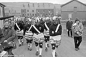"The ""Nutters' Dance"", Bacup, Lancashire  1973.  On Easter Saturday every year the ""Coco-nut"" dancers gather at one boundary of the town and dance their way across to the other accompanied by members of the Stackstead Silver Band, collecting for charity as they go.  Here they're taking a break and walking to the next spot."