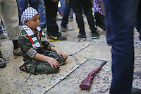 A Palestinian child pray while his toy gun laid on the ground in the old city of Jerusalem on September 13, 2013. Israeli police declared an age limit on Friday for Palestinians wanting to enter the Old City, only allowing males above the age of 45 and all females to enter, as Yom Kippur, the Jewish day of atonement, begins at sundown. Photo by Oren Nahshon