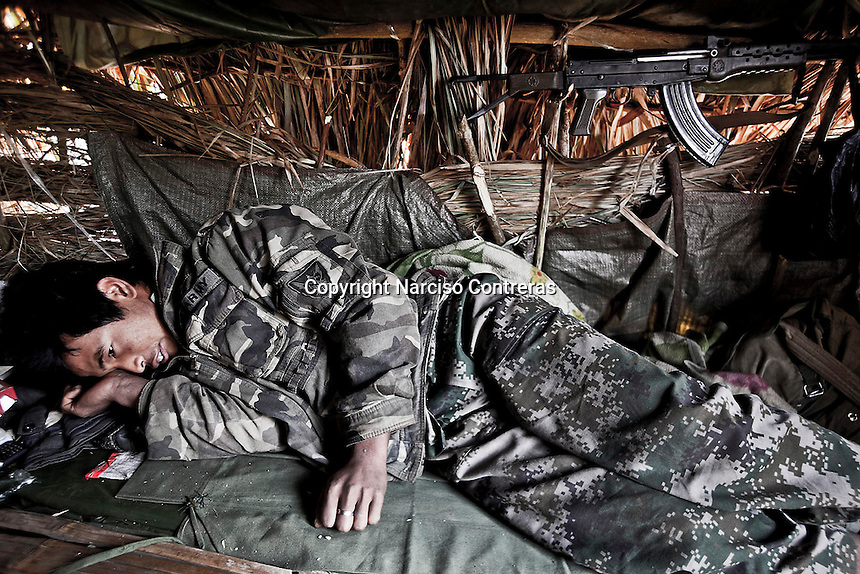 A KIA soldier rests from his duty in Maiya Jang front line at the top of the mountains, the second largest city under control of the Kachin Independence Army. The KIA positions around the city have been attacked by shelling and heavy artillery during last months. Fierce clashes have taken place since the ceasefire was broke by the Burmese army last June 2011. During months the fighting were spread out along the Kachin State leaving more than 40,000 displaced persons and refugees (a conservative estimating) in accord with the humanitarian aid groups.