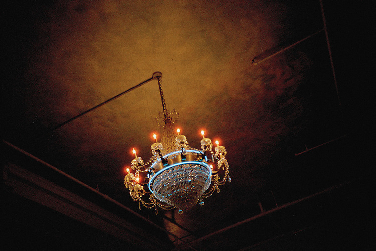a chandelier hangs from the ceiling of a dark room