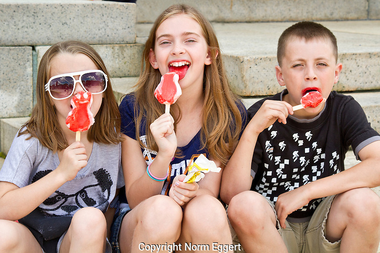Three children enjoy ice cream on a hot summer day