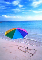 Tropical paradise Umbrella on the beach with hearts drawn in the sand