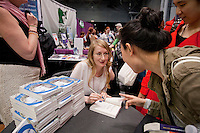 HSKU 20140531 United Stated, New York. Book Expo America, Javits Center. Finnish author Emmi Itaranta signs copies of her novel in English. Photographer: David Brabyn