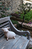 A jovial ceramic pig graces a weathered wooden bench in the courtyard garden
