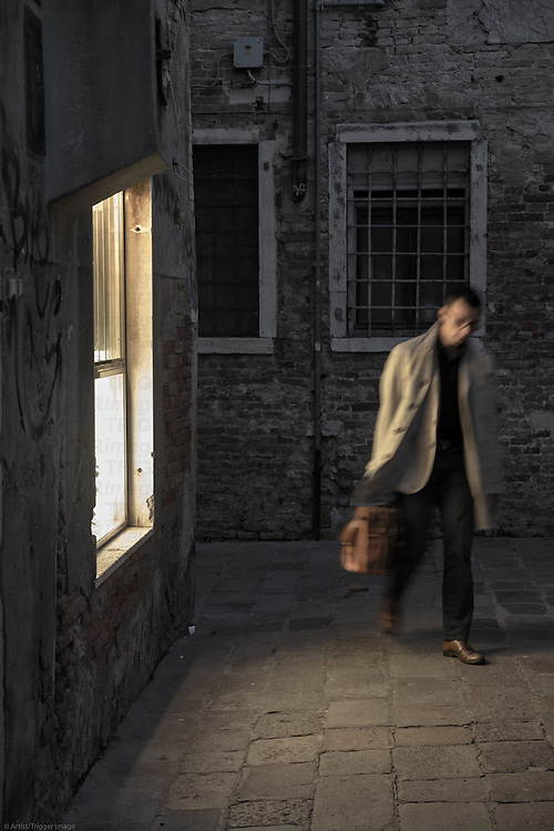 A solitary man carrying a briefcase walks in a dark Venice passageway and is illuminated by light as he strolls past a window.