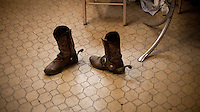 A paired of spurred cowboy boots sit on an office floor in a feedyard in Mead, Kansas. A feedyard is part of the factory farming process where animals are fattened up prior to slaughter. They are mostly fed on corn or corn dervived products gaining between 2.5 and 4.5 pounds per day. 25% of all American beef is produced in Kansas.