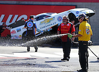 Apr 12, 2015; Las Vegas, NV, USA; A member of the NHRA safety safari sprays water in the burnout box as funny car driver John Force is pushed into position during the Summitracing.com Nationals at The Strip at Las Vegas Motor Speedway. Mandatory Credit: Mark J. Rebilas-