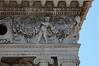 Corner of the sculpted frieze of putti above the first floor Ionic arcade of the Biblioteca Nazionale Marciana, or National Library of St Mark's, built in Renaissance style in 1537-53 by Jacopo Sansovino, then extended by Vincenzo Scamozzi in 1588, on the Piazzetta San Marco, between the Piazza San Marco and the Venetian lagoon, Venice, Italy. The columns are topped with Ionic capitals and the spandrel figures are angels in classical or all'antica style, and above, puttis hold decorative garlands, with classical masks. The 2-storey building is lined with a Doric arcade on the ground floor and Ionic arcade on the first floor, with sculptural decoration and a line of rooftop statues. The library houses an important collection of classical, Oriental and medieval codices and manuscripts. The historical centre of Venice is listed as a UNESCO World Heritage Site. Picture by Manuel Cohen