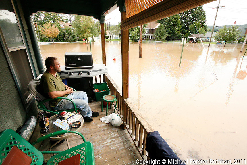 Skeet Wood watches the water rise from his porch on Clinton Street in Sidney, NY, as the Susquehanna River overflows its banks. Flooding from the Susquehanna River led to the closing of Interstate 88 in Otego, NY, and forced evacuation of the flooded downtown in Sidney, NY, on Sept. 8, 2011. The Susquehanna River continued to rise Thursday afternoon, with periods of heavy rain in upstate New York due to Tropical Storm Lee.<br /> &copy; Michael Forster Rothbart Photography<br /> www.mfrphoto.com &bull; 607-267-4893<br /> 34 Spruce St, Oneonta, NY 13820<br /> 86 Three Mile Pond Rd, Vassalboro, ME 04989<br /> info@mfrphoto.com<br /> Photo by: Michael Forster Rothbart<br /> Date:  9/2011    File#:  Canon 5D digital camera frame 70458