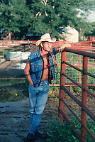 Cowboy standing in a muddy pen