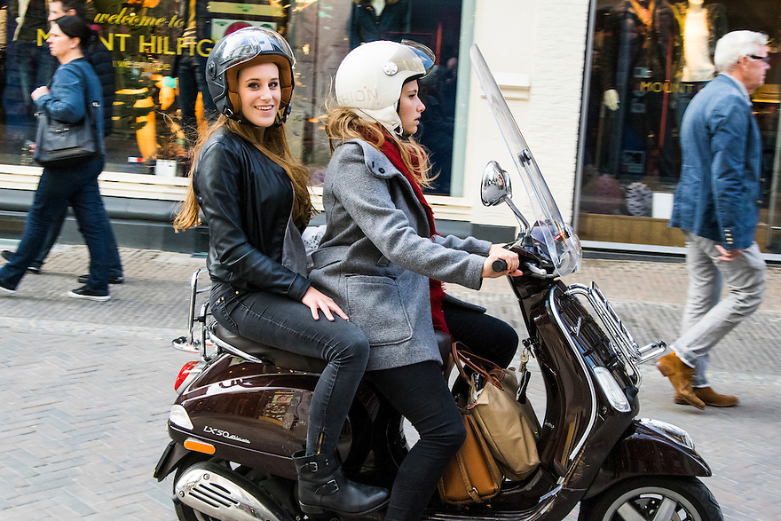 Nederland, Utrecht, 10 okt 2014<br /> Mensen op straat. Meisjes op scooter in de stad. Scooters stoten veel schadelijke stoffen uit.<br /> Foto: (c) Michiel Wijnbergh