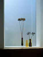 Coloured glass vases filled with Agapanthas against acid-etched glass panes create a decorative focus