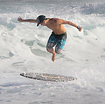 A boarder dances off his skim board in the off the shores of Sandy Beach in Hawaii during high-tide.