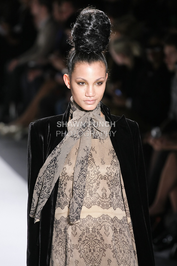 Model walks runway in a black silk velvet upturned peak lapel floor length coat lined w/silk mouseeline lace, and nude+black silk mousseline lace print sleeveless A-line gown w/bow, from the Zang Toi Fall 2011 Timeless Beauties collection, during Mercedes-Benz Fashion Week Fall 2011.