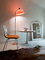 A standard lamp with an orange shade casts a warm light over the chair and Saarinen table