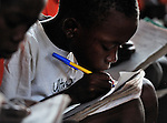 "A boy writes in his notebook in a primary school class in Chidyamanga, a village in southern Malawi that has been hard hit by drought in recent years, leading to chronic food insecurity, especially during the ""hunger season,"" when farmers are waiting for the harvest."
