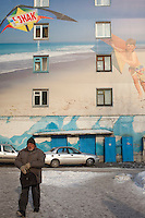 Barnaul, Altai Region, Siberia, Russia, 24/02/2011..City centre apartment building with wall covered by giant photo mural of beach scene.