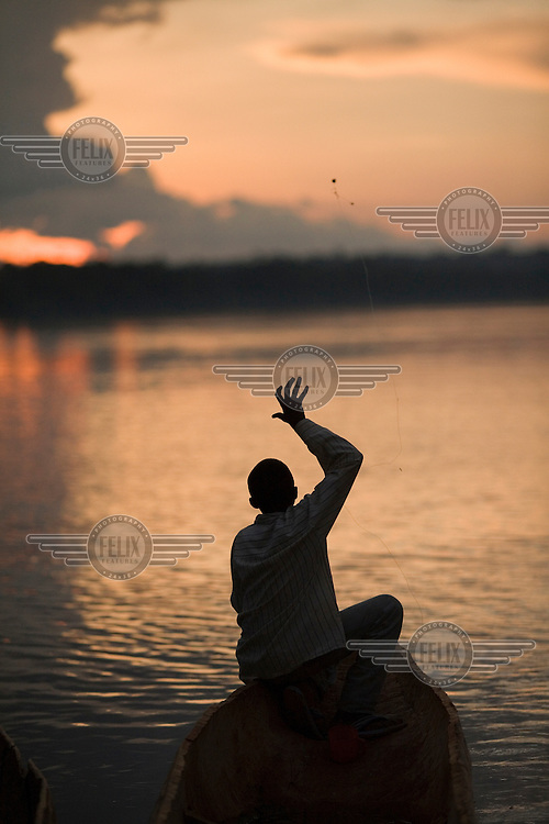 With the light fading, a  boy in a canoe casts his fishing net into the Mbomou river.