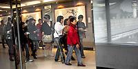 Group of Asian passengers walking through Taipei International Airport.