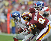 Landover, MD - November 30, 2008 -- New York Giants quarterback Eli Manning (10) is sacked by Washington Redskins defender Anthony Montgomery (94) in the first quarter at FedEx Field in Landover, Maryland on Sunday, November 30, 2008..Credit: Ron Sachs / CNP.(RESTRICTION: No New York Metro or other Newspapers within a 75 mile radius of New York City)