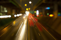 Cinematic view using anamorphic lens of speeding traffic on Austin's upper and lower deck of I-35 transportation corridor in downtown Austin, Texas.