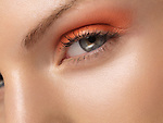 Closeup of a young beautiful woman eye with orange makeup