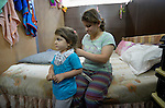 Four-year old Bahar Nawar gets her hair brushed by Hanen Yousif in the basement of Sacred Heart Catholic church in Amman, Jordan, where 60 Iraqi Christian refugees are living. The Lutheran World Federation, a member of the ACT Alliance, has helped the church feed the refugees and remodel the basement into partitioned areas to provide some privacy for the ten refugee families.<br /> <br /> Parental consent obtained.