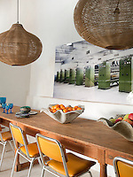 A large contemporary photograph of factory machinery is displayed on the wall behind the dining room table