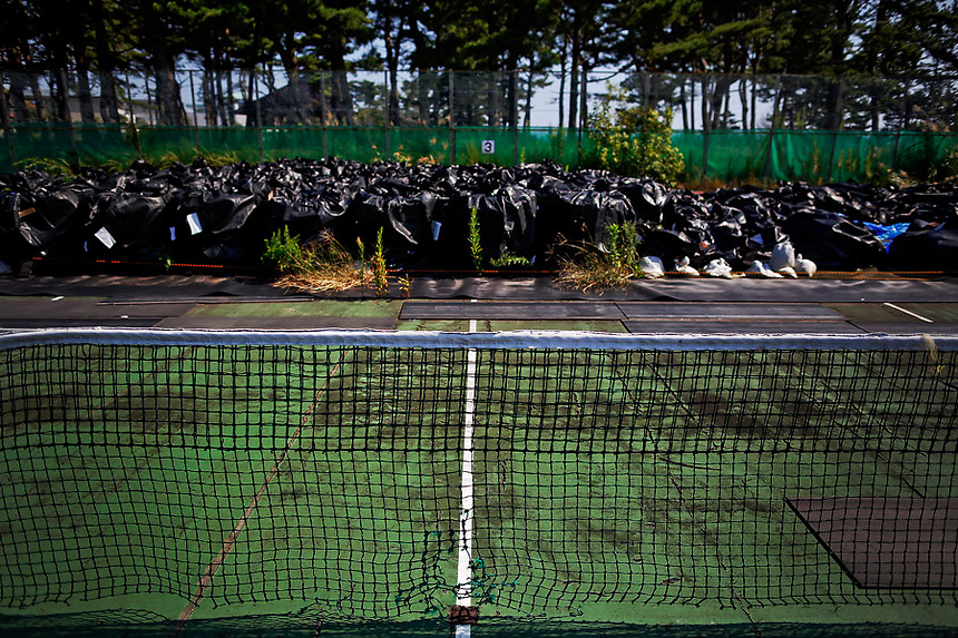 Big plastic bags containing radiated soil, leaves and debris from the decontamination operation are dumped at the tennis court at sport park in Naraha town, which is inside the formerly no-go zone of a 20 km (12 mile) radius around the crippled Fukushima Daiichi nuclear power plant September 21, 2013. The most ambitious radiation clean-up ever attempted has proved costly, complex and time-consuming since the Japanese government began it more than two years in the wake of the Fukushima nuclear meltdown. It may also fail. There is also the problem of storage. Most of the contaminated soil and leaves remain piled up in driveways and empty lots because of fierce opposition from local communities to storing it in one place until the Ministry of Environment secures a central site that could hold it for the longer term.  REUTERS/Damir Sagolj (JAPAN)