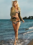 Young beautiful woman with long blond hair running gracefully along the beach