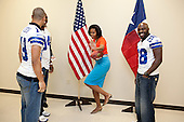 First Lady Michelle Obama strikes the Heisman pose while greeting Dallas Cowboy football players, from left, Miles Austin, DeMarcus Ware, and Felix Jones at the Kleberg Rylie Recreation Center in Dallas, Texas, February 10, 2012. The players joined Mrs. Obama and chefs from past seasons of Top Chef for the Schools and Chefs Working Together cooking competition to help promote the Lets Move! initiative. .Mandatory Credit: Chuck Kennedy - White House via CNP
