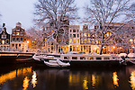 Evening light on the snow covered streets and canals of Amsterdam, the Netherlands.