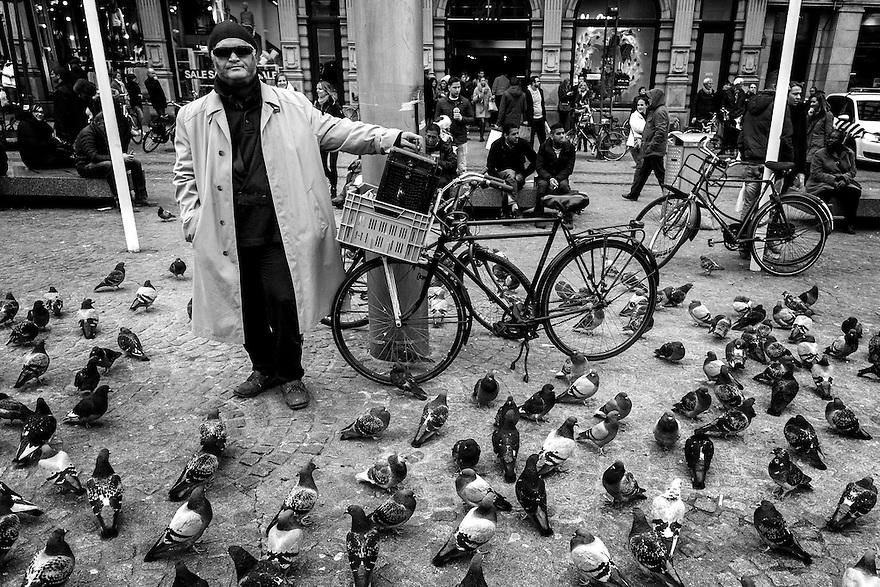 Nederland, Amsterdam, 13 dec 2014<br /> Man op de dam en zijn fiets tussen de duiven. <br /> Foto: (c) Michiel Wijnbergh