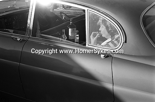 Epsom Downs, Surrey. 1970<br /> Derby Day, in the car park and before the Off, a racegoer enjoys a Gordon's Special Dry London Gin and tonic and a cup cake in the back of the Jaguar.