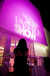 An attendee of the 2011 Victoria's Secret Fashion Show viewing party Tuesday night takes a picture of the side of the Samueli Theater at the Segerstrom Center of the Arts before the start of the show.