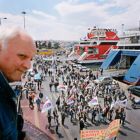 An old man watching a demonstration of Piraeus Port workers and the confederation of Greek workers during the financial crisis.