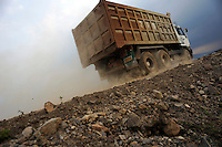 A truck rumbles along the ridge of an earthen dam which holds in millions of gallons of liquid mud flow. Since May 2006, more than 10,000 people in the Porong subdistrict of Sidoarjo have been displaced by hot mud flowing from a natural gas well that was being drilled by the oil company Lapindo Brantas. The torrent of mud - up to 125,000 cubic metres per day - continued to flow three years later.