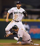 Seattle Mariners second baseman Dustin Ackley connects on a double play against  Oakland Athletics Seth Smith in the second inning at SAFECO Field in Seattle April 13, 2012.  © 2012. Jim Bryant Photo. All Rights Reserved.
