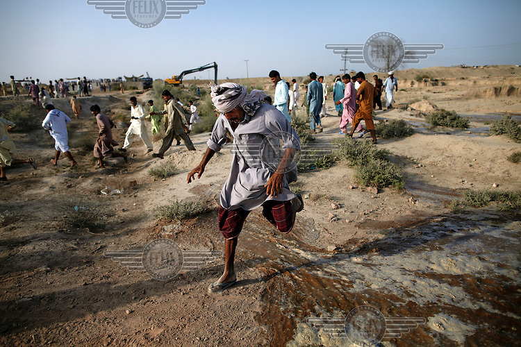 A man jumps over flood water as it inundates the surrounding area after Manchar Lake bursts its banks. Officials  made a breach in the lake's embankments to direct water away from the nearby cities of Dadu and Sehwan, in Sindh Province, Pakistan.