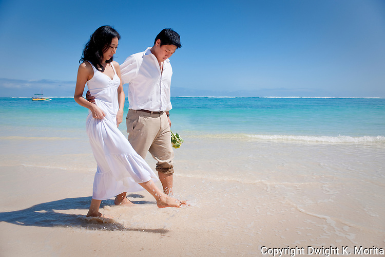 Asian bride and groom kick up water during their walk on Lanikai beach. The couple celebrate their wedding with a honeymoon in Hawaii.