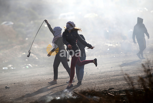 Female Palestinian protesters throw stones at Israeli troops during clashes near the Jewish settlement of Bet El, near the West Bank city of Ramallah, October 29, 2015. Israeli security forces shot dead two Palestinian assailants in the occupied West Bank on Thursday, police and the army said, as a month-long spate of stabbing attacks showed no signs of abating. Photo by Shadi Hatem
