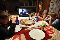 HIGHLAND | GySgt. Ryan Ralph joins his family for dinner via Skype at the Ralph's home in Highland on Wednesday, Feb. 9, 2011. Sherri Ralph prays for dinner with sons D.J. Mendoza, left, and Matthew Mendoza, 8, right, before they eat pizza, Ryan Ralph's favorite.
