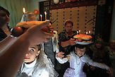 Zwei Mädchen  drehen sich unter Platten mit Gebbäck und Kerzen während einer Hochzeitszeremonie in Kant, Kirgisistan. Die Überlieferung sagt, dass es dann  Licht und Wohlstand für das Paar geben wird. / Two girls whirl under plates during a wedding ceremony in Kant, Kyrgyzstan.  Tradition says that having young girls swirl under a plate full of traditional treats will bring light and prosperity to the new couple's life. The plates are layered with candies, cookies, apples, and a butter bread called Kete. They light candle on top of the bread.