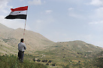 A Druze man holds a Syrian flag during a pro-Syrian demonstration on the Syrian independence day, standing in front of Syrian soil in Majdal Shams, Golan Heights, on Israel-Syria border.