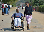 Caroline Mandishona (left) moves along a street near her home in Bulawayo, Zimbabwe. Mandishona suffered cerebral palsy and uses a wheelchair provided by the Jairos Jiri Association with support from CBM-US. She is accompanied by Silindeni Gama, a community rehabilitation worker for Jairos Jiri.