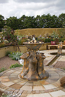 Patio with different types of pavers, water fountain feature, garden wall, stone