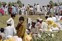 Refugees from Swat district wait for food distribution at the Swabi Refugee camp. The camp is run by Red Cross/Red Crescent (ICRC), and currently houses around 18,000 refugees. The Pakistani government began an offensive against the Taliban in the Swat Valley in April 2009, which led to a major humanitarian crisis. Up to two million civilians were estimated to have been displaced by the fighting.
