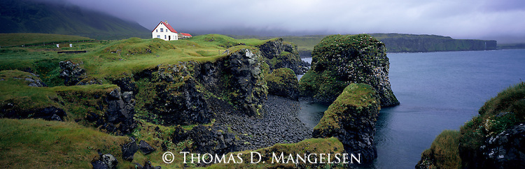 A farmhouse sits on cliffs above the ocean in Arnarstapi in West Iceland.