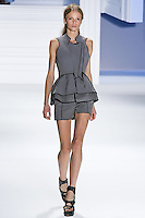 Morgane Warnier walks runway in a Charcoal super pique tailored vest over perforated corset and skirted short, by Vera Wang, for the Vera Wang Spring 2012 collection, during Mercedes-Benz Fashion Week Spring 2012.